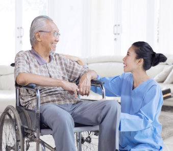 caregiver and an elderly man on a wheelchair chatting