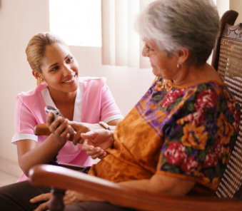 caregiver checking up an elderly woman sitting on a rocking chair
