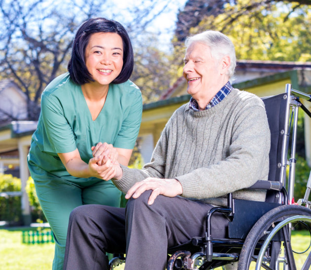 caregiver and an elderly man on a wheelchair smiling at the camera