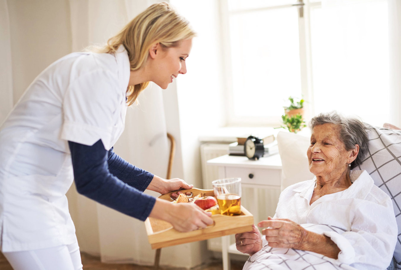 caregiver serving meal to an elderly woman