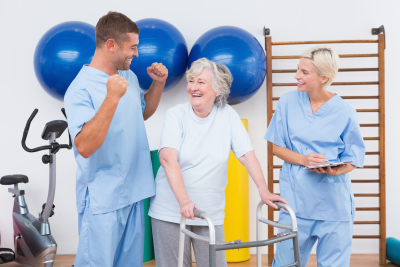 male and female caregiver with senior woman smiling